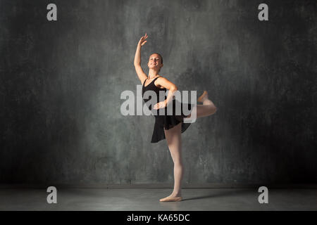 Beautiful attractive blonde woman baterina in a black dance tutu, white pantyhose and pointe shoes beautifully dances - Stock Photo