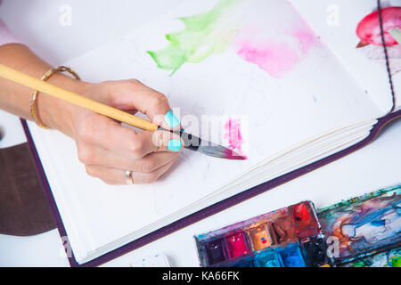 A close-up as an artist with blue nails draws pink flowers with a wooden brush and watercolors in the aluoma for - Stock Photo