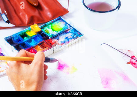 A close-up artist paints pink flowers with a wooden brush and watercolors in the drawing album, on the table lie - Stock Photo