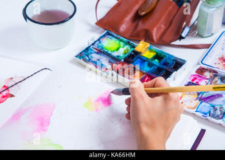 A close-up as an artist draws pink flowers with a wooden brush and watercolors in a drawing pad, on the table lie - Stock Photo
