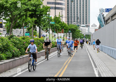 Recreational cyclists riding on the Hudson River Greenway on the west side of Manhattan, New York City, USA. - Stock Photo