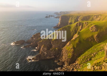 Mull of Oa, Islay, Scotland, in evening time with nice warm light, fog is comming in over the cliffs, gren grass - Stock Photo