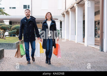 Couple in shopping time walking in the city street - Stock Photo