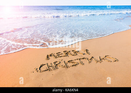 merry christmas written in the sand at the seashore on the beach stock photo - Merry Christmas Beach Images