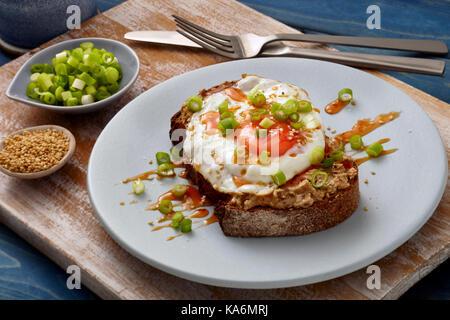 Honet sriracha fried egg on toast - Stock Photo