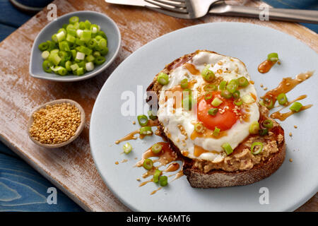 Honey sriracha fried egg on toast - Stock Photo