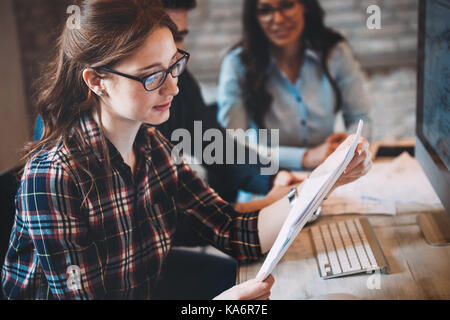 Happy woman in office looking at blueprint - Stock Photo