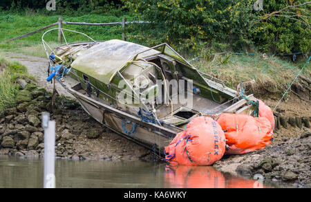 Small boat wreck abandoned on the bank of a river. - Stock Photo