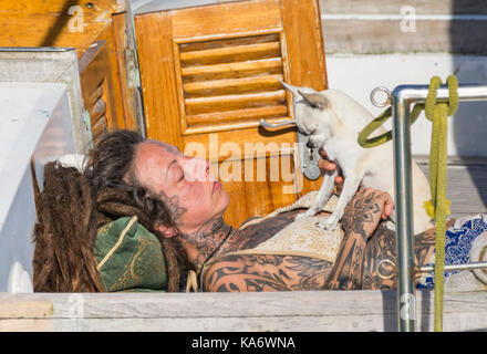 Woman with tattoos laying on a boat in the sun with a dog. - Stock Photo