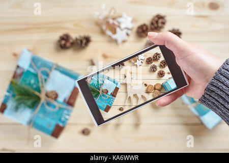 Woman's hand taking photo of Christmas decorations and gifts by smartphone - Stock Photo