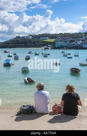 St Ives - holidaymakers relaxing on the quayside and enjoying the view over St Ives Harbour in Cornwall. - Stock Photo