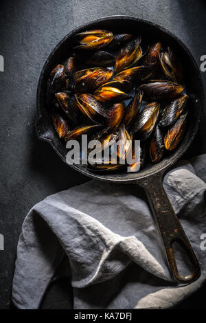 Mussels on a cast-iron frying pan and napkin on a gray background vertical - Stock Photo