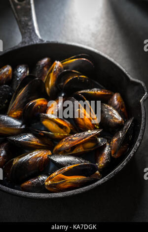Mussels on a cast-iron frying pan on a gray background close-up vertical - Stock Photo