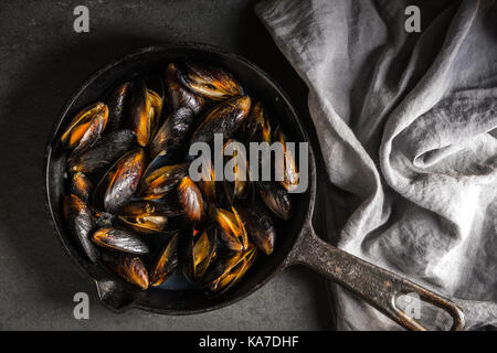Mussels on a cast-iron frying pan and napkin on a gray background diagonal horizontal - Stock Photo