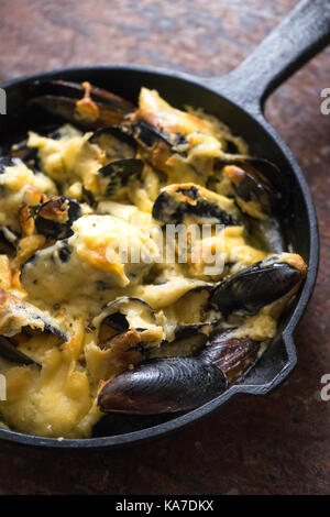 Frying pan with mussels under a cheese sauce on a brown background diagonal vertical - Stock Photo