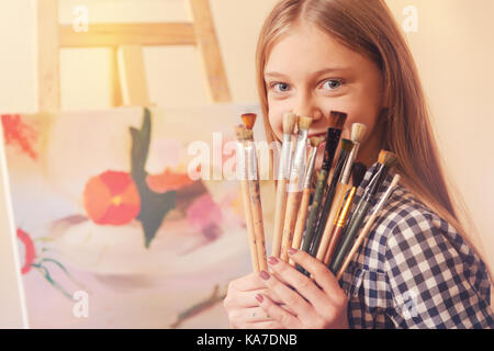 Beautiful girl hiding her face behind painting brushes - Stock Photo