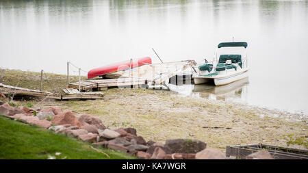 Wrecked Dock & Damaged Boat on Water After Storm - Stock Photo