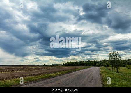 Mysterious clouds are flying very low over an old country road. Countryside landscape - Stock Photo