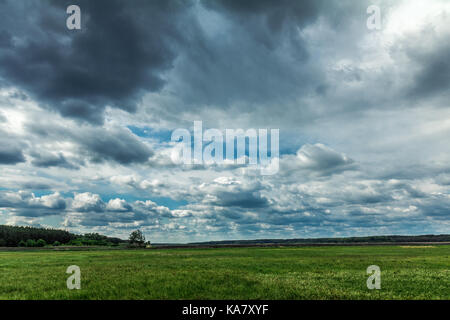 Fluffy rain clouds flying on a bright blue sky over a green field. Countryside landscape - Stock Photo