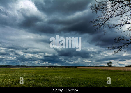 Dark heavy stormy clouds have covered the sky over the field. Countryside landscape - Stock Photo
