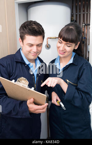 Female Trainee Plumber Working On Central Heating Boiler With Male Engineer - Stock Photo