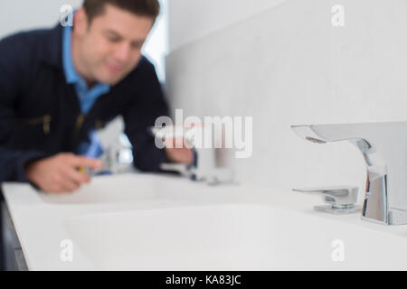 Plumber Working On Sink Using Wrench In Bathroom - Stock Photo