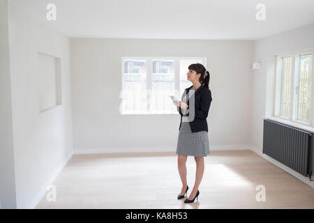 Female Estate Agent With Digital Tablet Looking Around Vacant Property For Valuation - Stock Photo