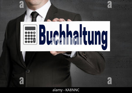 Buchhaltung (in german Accounting) signboard is held by businessman. - Stock Photo