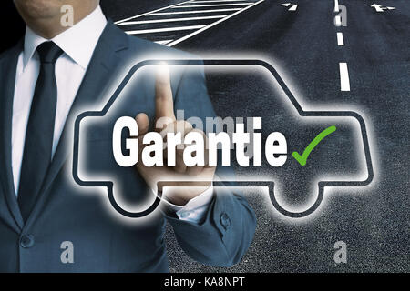 Garantie (in german Warranty) with car touchscreen is operated by man. - Stock Photo