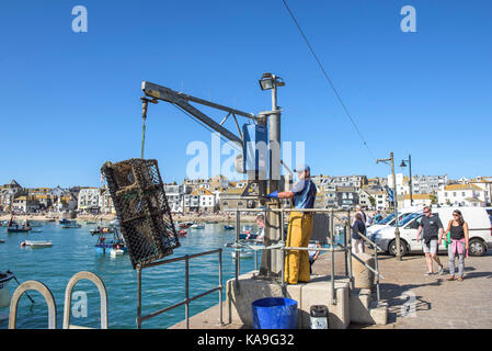 St Ives fishing industry - a fisherman using a hoist to unload crab lobster pots on Smeatons Pier in St Ives in - Stock Photo