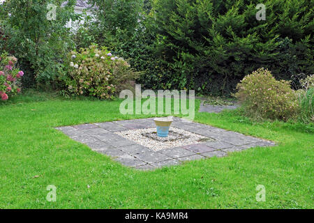 Weeds growing in a single blue ceramic garden pot carefully placed in the centre of a green patch of lawn with gravel - Stock Photo