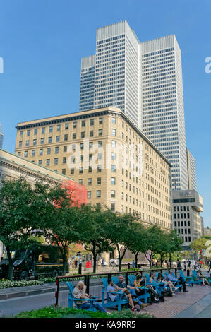 People sitting outdoors on McGill College Avenue with Confederation Building and Place Ville Marie office tower - Stock Photo