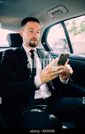 A businessman while traveling by car in the back seat, send a message or email and calls. The man in the driver - Stock Photo