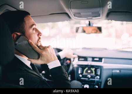 Man using his phone while driving the car - Stock Photo