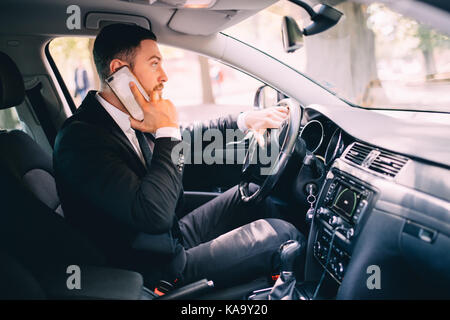 Business man driver speak phone white drive car - Stock Photo