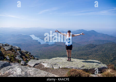 Female hiker standing on the edge of a cliff with her arms out at the summit of Whiteface Mountain - Stock Photo