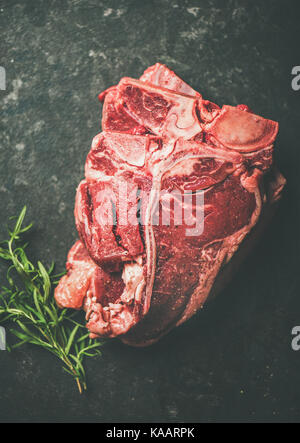 Fresh raw beef meat t-bone steaks with rosemary, black background - Stock Photo