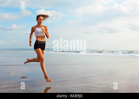 Barefoot sporty girl with slim body running along sea surf by water pool to keep fit, health. Beach background with - Stock Photo