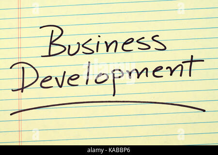 The word 'Business Development' underlined on a yellow legal pad - Stock Photo