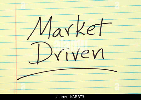 The word 'Market Driven' underlined on a yellow legal pad - Stock Photo