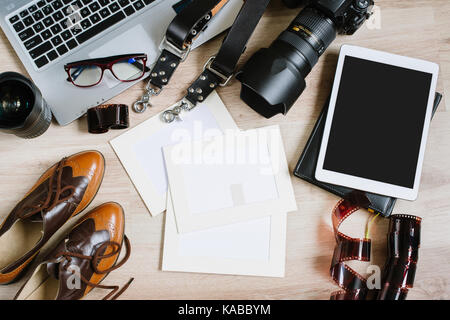 photographer desk with lenses and laptop computer in the
