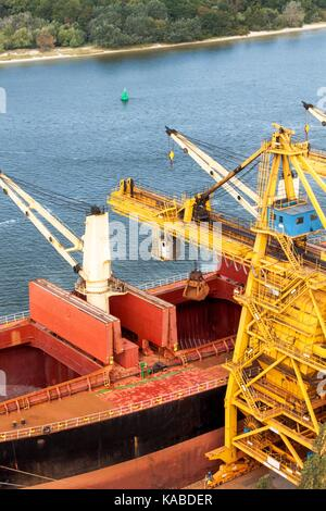 Crane unloads iron ore at the harbor. Trade in raw materials. Work at a port in the Baltic Sea - Stock Photo