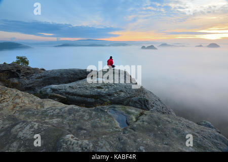 Hiker on rock end above valley. Man watch over misty and autumnal morning valley to bright morning Sun. Tourist - Stock Photo