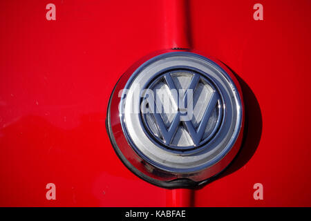 VW Car Badge On The Front Of A Red Volkswagen Beetle - Stock Photo