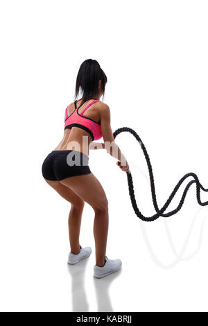 Athletic young woman doing crossfit exercise with rope isolated on white background - Stock Photo