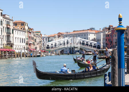 Three gondoliers rowing their gondolas with tourists on the Grand Canal near the  Rialto Bridge, Venice, Italy - Stock Photo