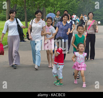 Young mothers and their children smiling and walking through Moranbong Park. Pyongyang, North Korea - Stock Photo