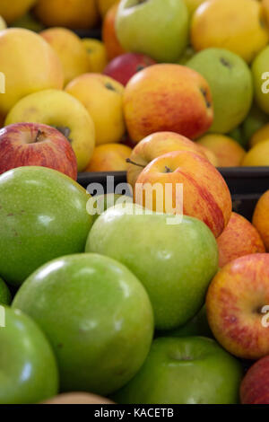 Various colours of apples for sale at a local fruit market in Portugal - Stock Photo