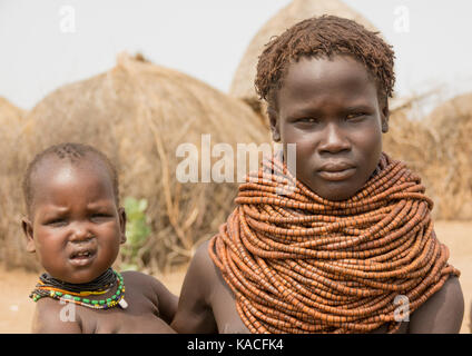 Young Nyangatom woman with her baby, Kangate, Omo Valley, Ethiopia - Stock Photo