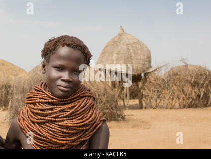 Young Nyangatom woman in her village, Kangate, Omo Valley, Ethiopia - Stock Photo